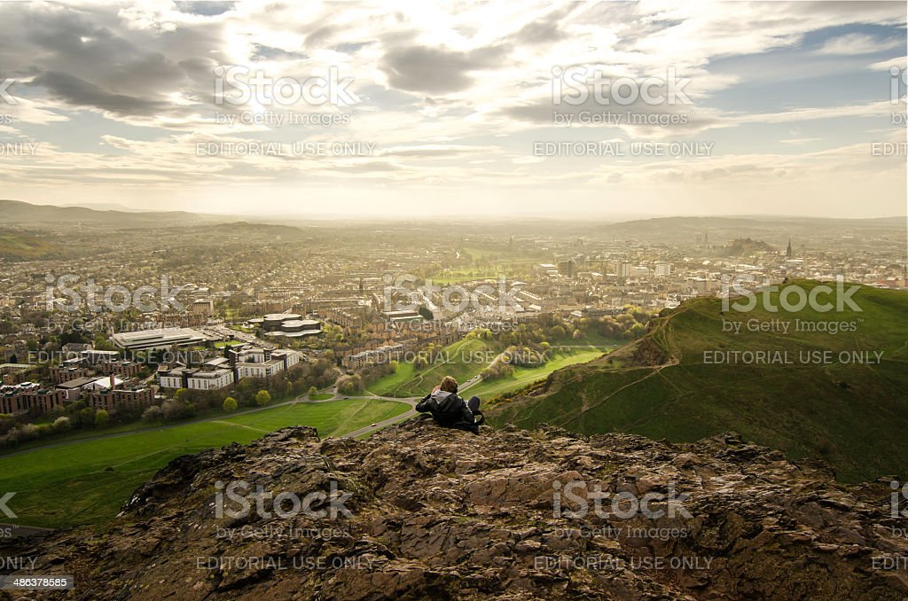 Boy sittng on the top of the Arthur's Seat stock photo