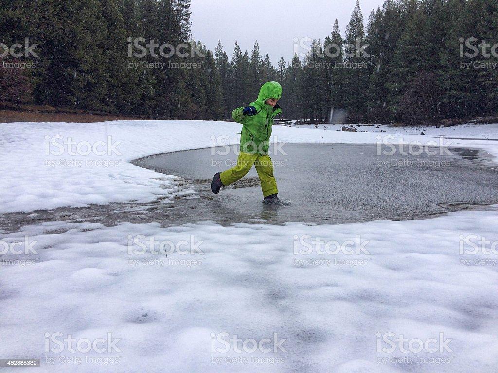 Boy slashing is icy slush stock photo