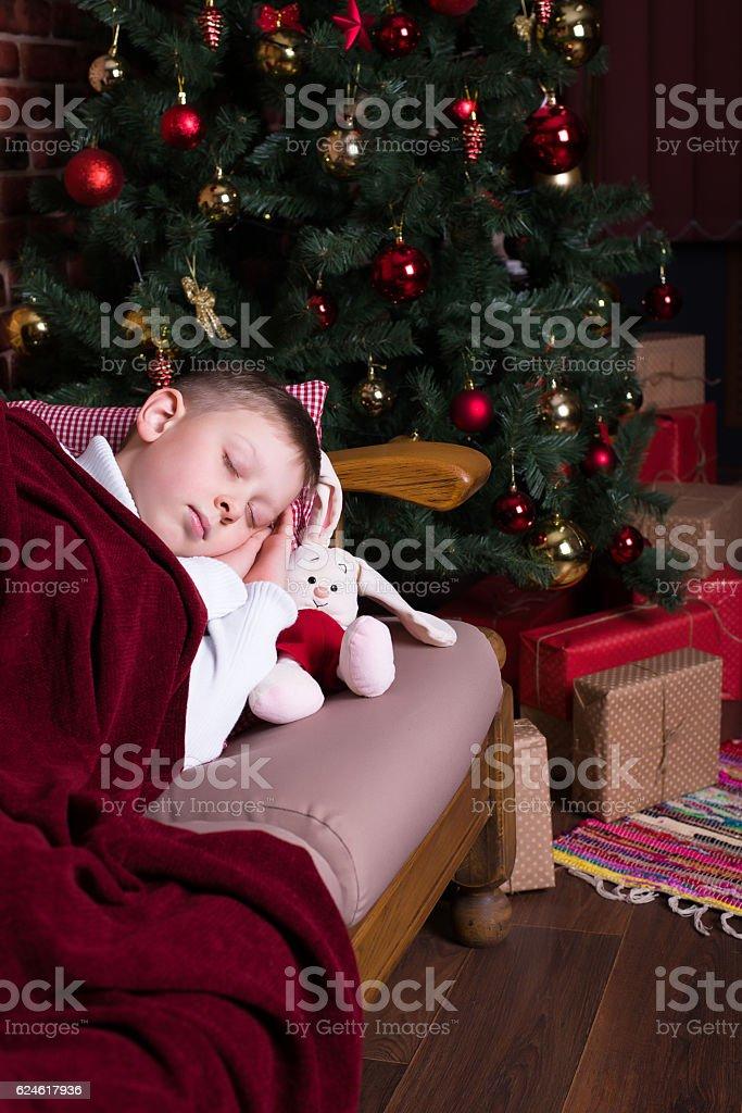 Boy sleeping on sofa near Christmas tree with gifts stock photo