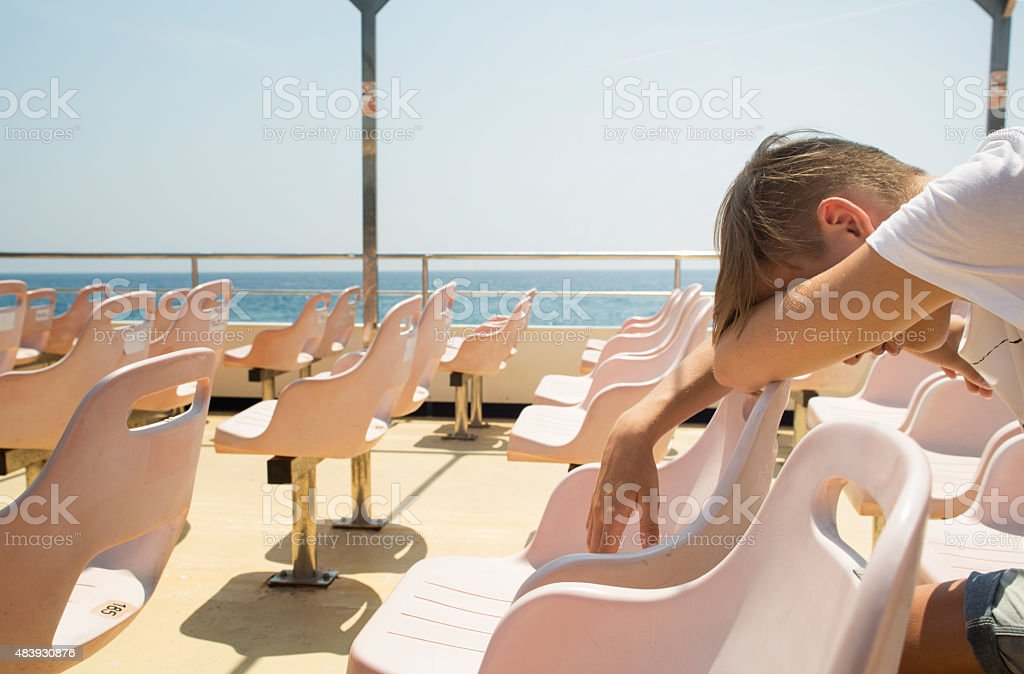Boy sleeping on the deck-chair stock photo