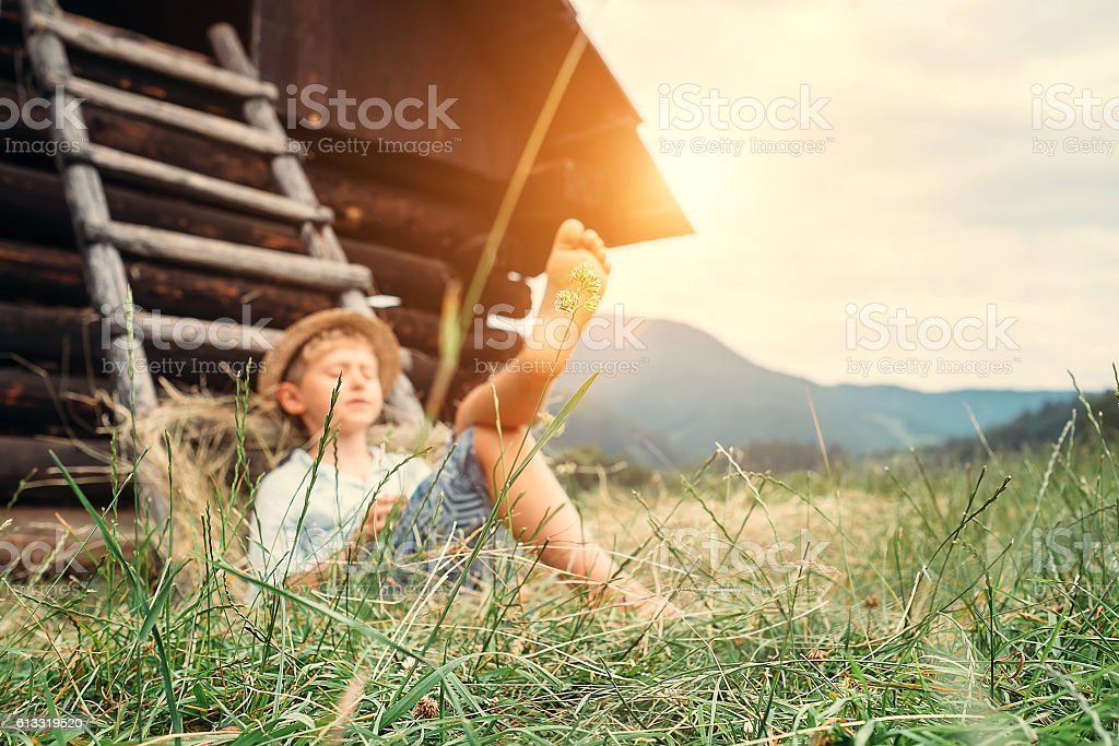 Boy sleeps in grass under hayloft in summer afternoon stock photo