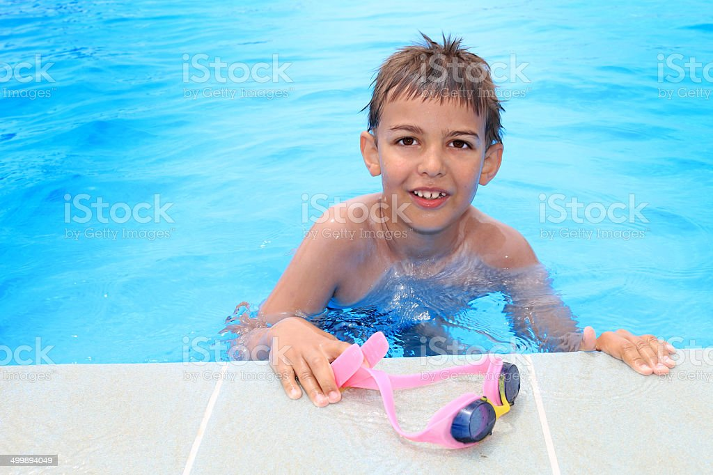 Boy smiling by the pool stock photo