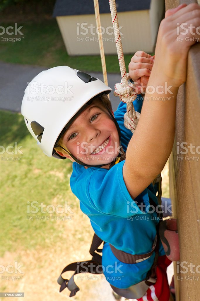 Boy Smiling While Climbing High Up On Tower / Rock Wall royalty-free stock photo