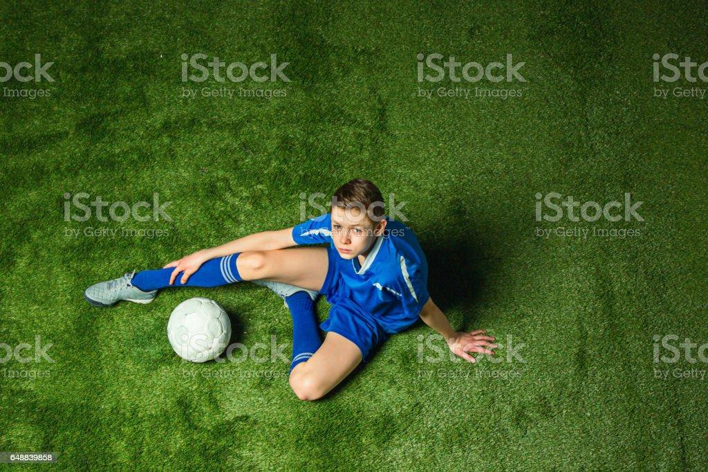 Boy soccer player sitting on green grass stock photo
