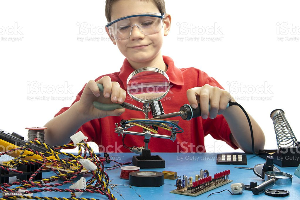 Boy soldering an electronic board stock photo