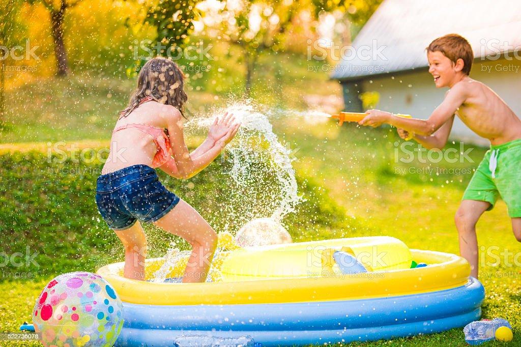 Boy splashing girl with water gun, garden swimming pool stock photo