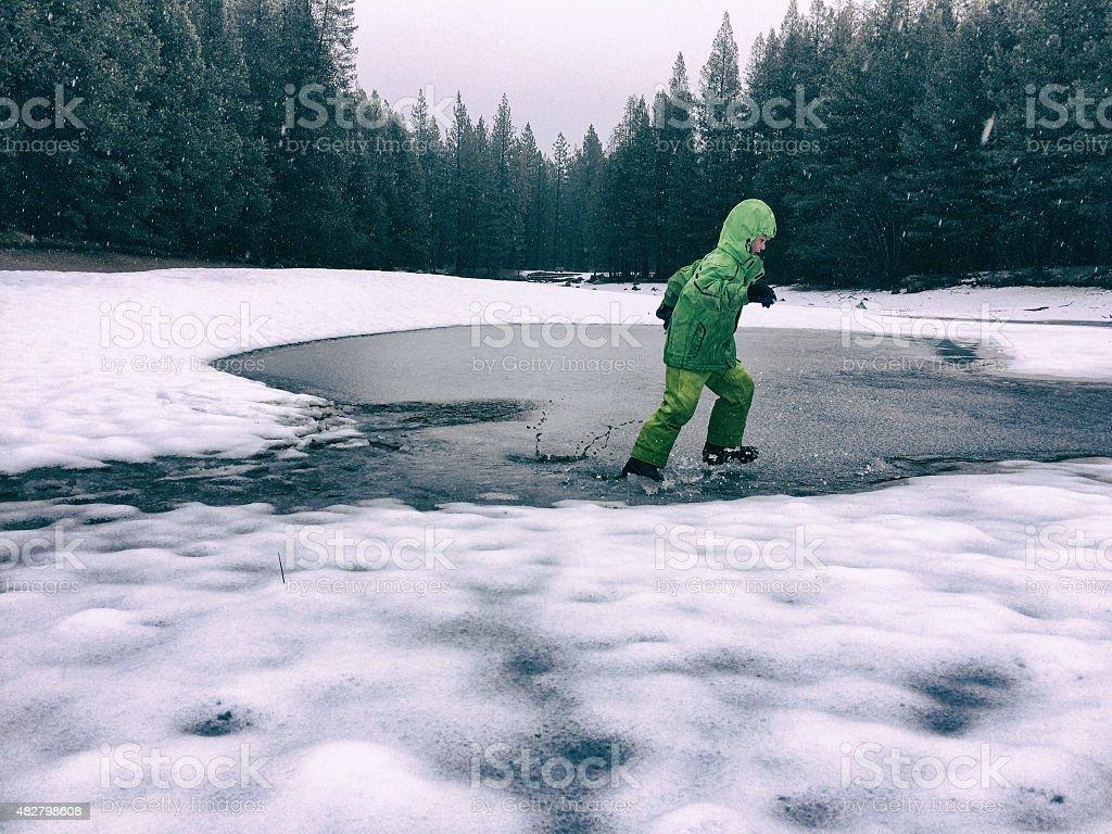 Boy splashing in icy pond stock photo