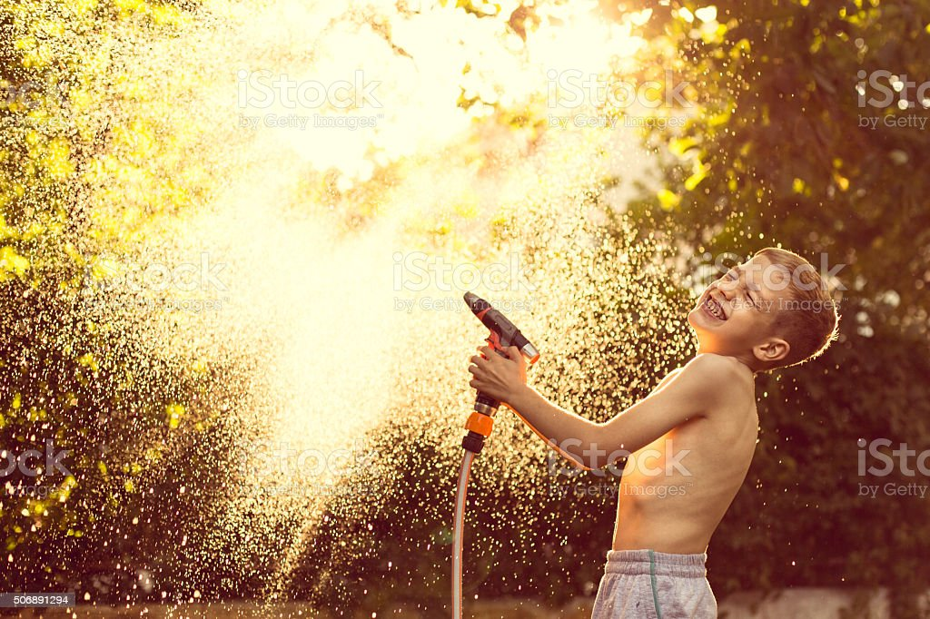 Boy splashing with water in garden stock photo