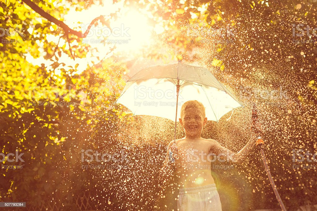 Boy splashing with water in garden stock photo
