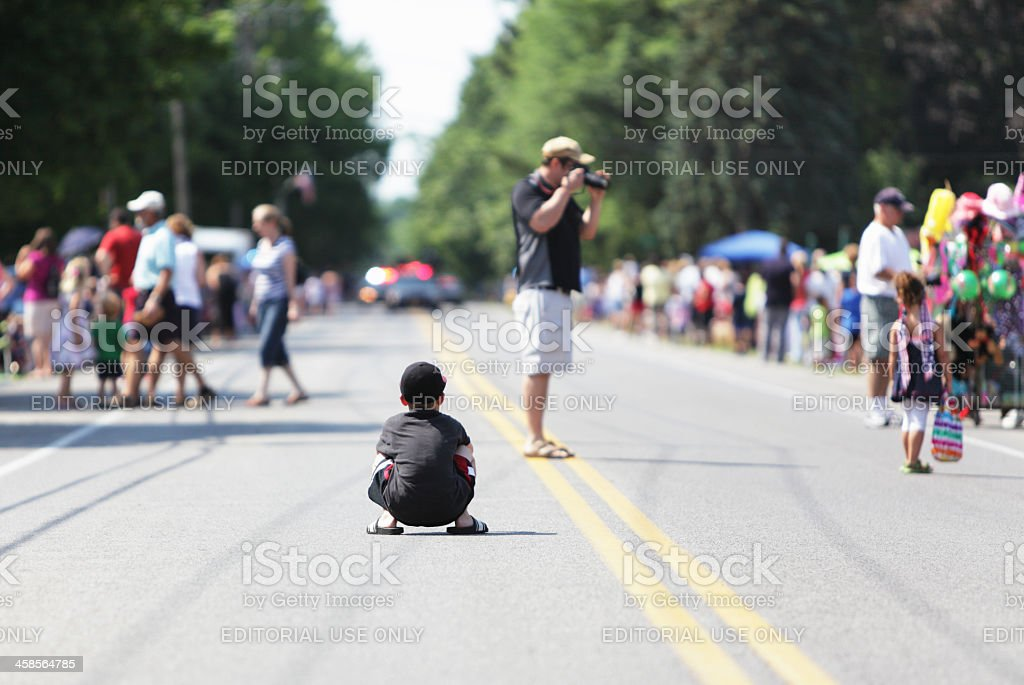 Boy Squatting on Road Waiting for Holiday Parade stock photo