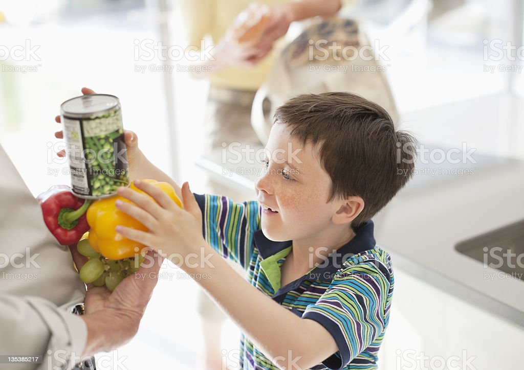 Boy stacking food into grandfather stock photo