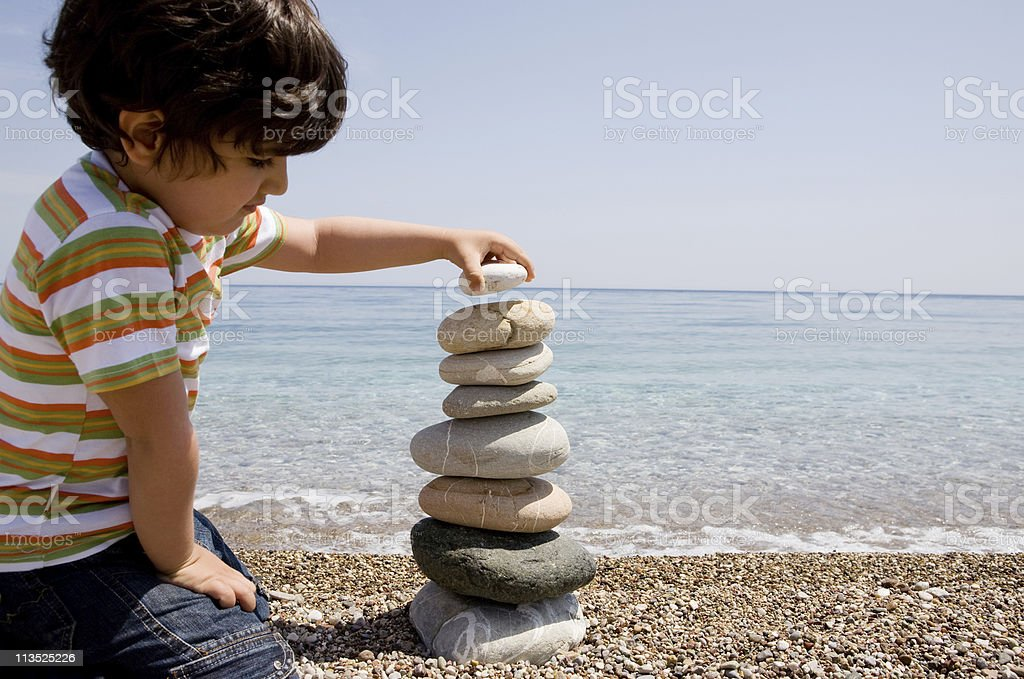 Boy stacking rocks royalty-free stock photo