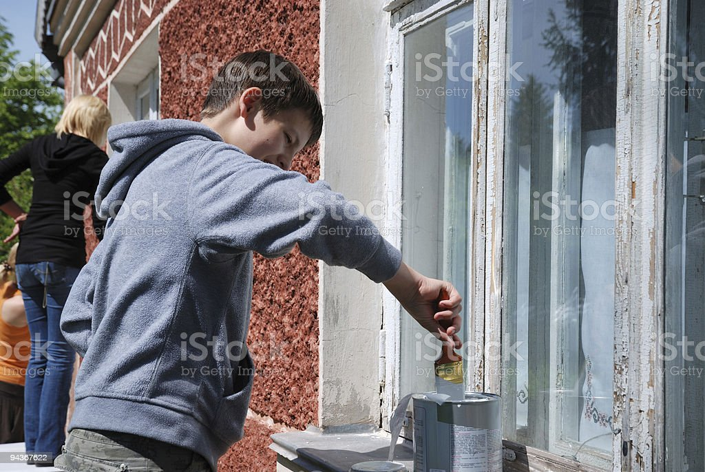 Boy staining window on the outside. stock photo
