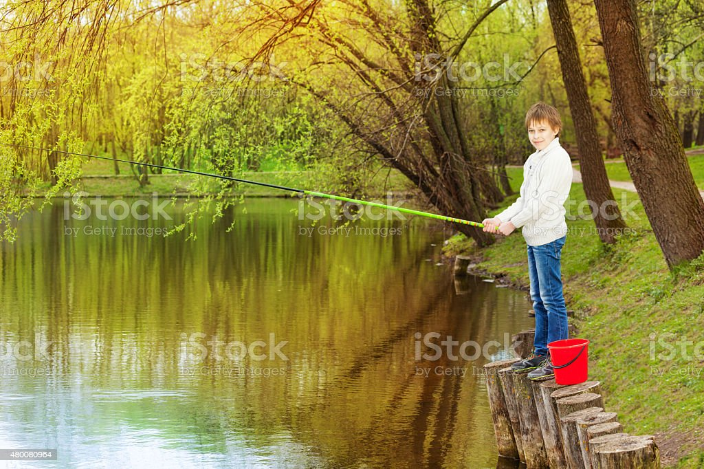 Boy standing and fishing near the pond stock photo