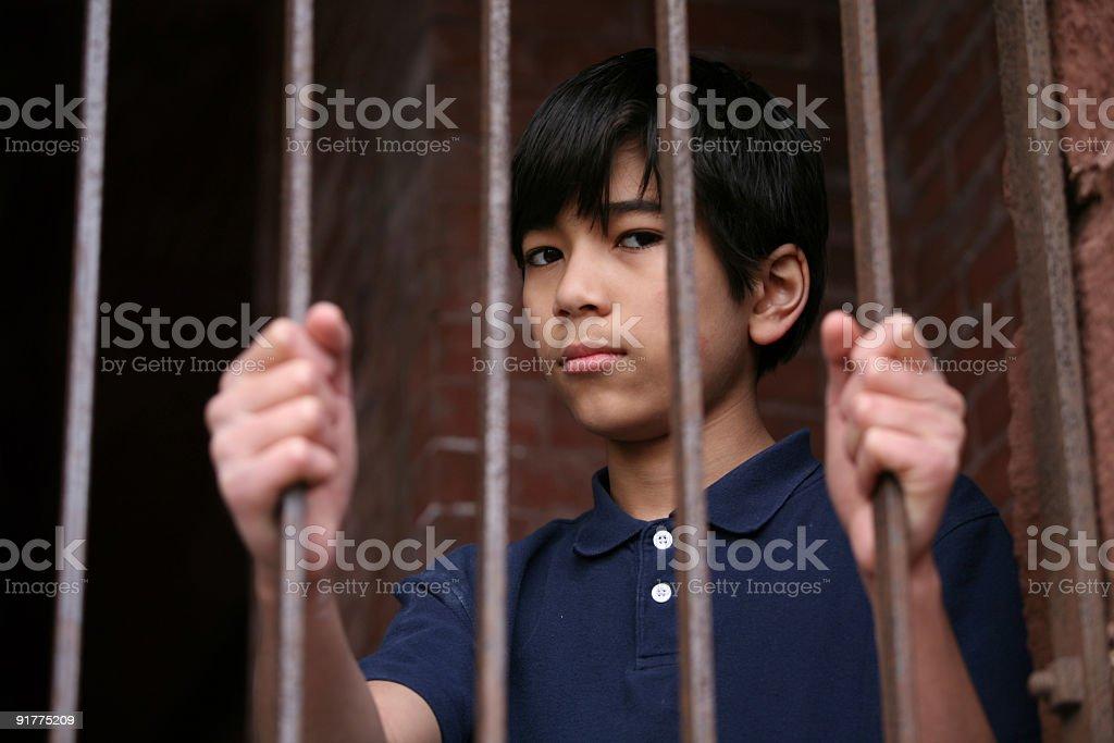 Boy standing behind bars stock photo