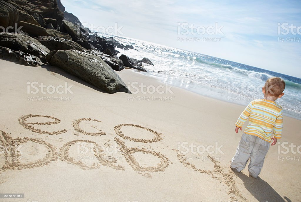 Boy Standing By Eco Baby written on sand stock photo