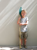 Boy standing by wall with fishing net, portrait