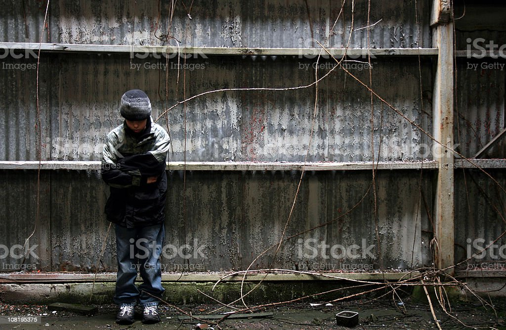Boy Standing in Grunge Alleyway Against Abandoned Building royalty-free stock photo