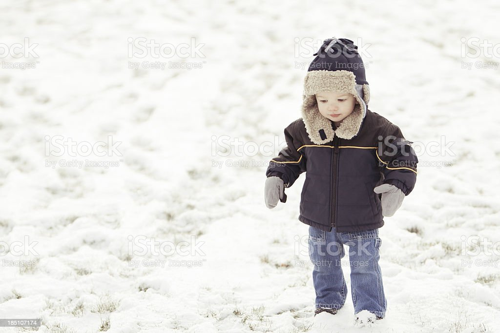 Boy standing in snow with winter hat stock photo