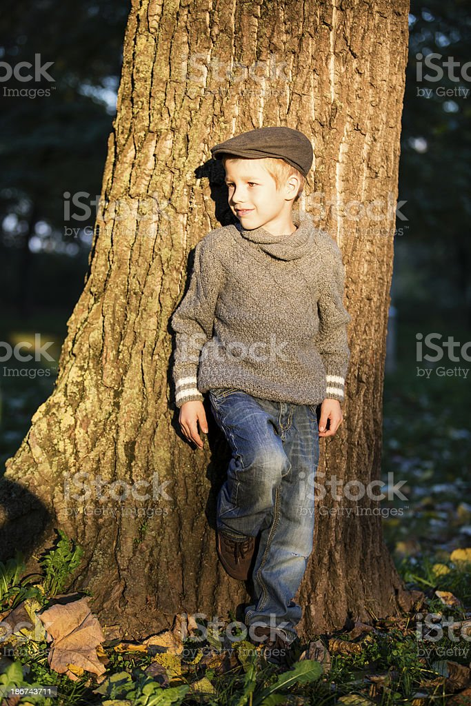 Boy standing next to the tree stock photo