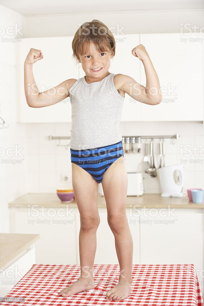 Boy Standing On Kitchen Table In Underwear stock photo