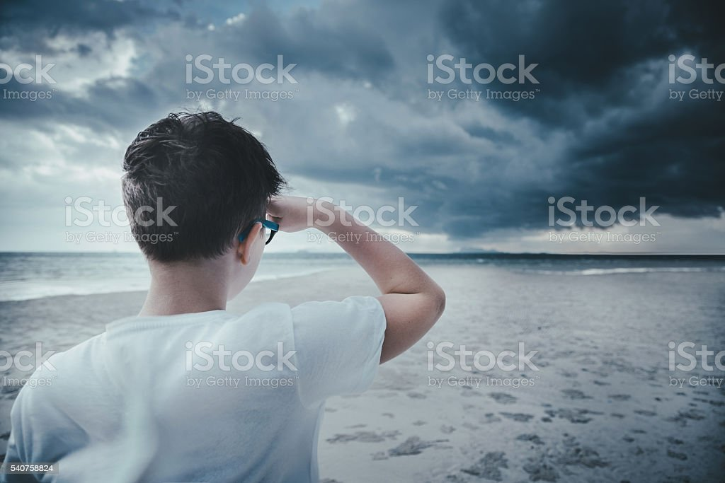 Boy standing on the beach and looking forward stock photo