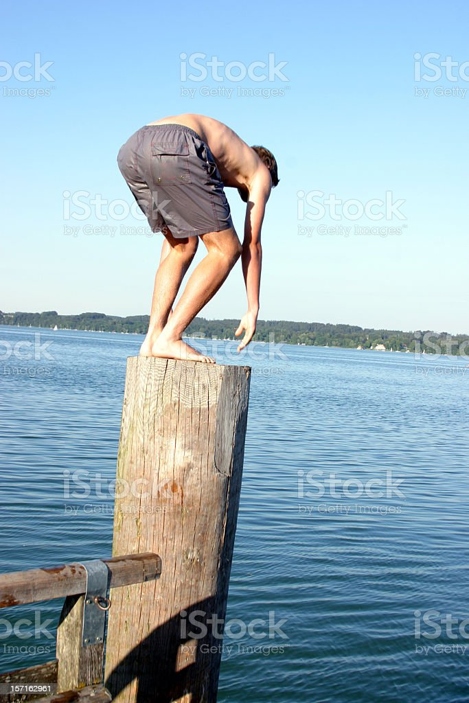 Boy standing on wooden column short before jumping into lake royalty-free stock photo