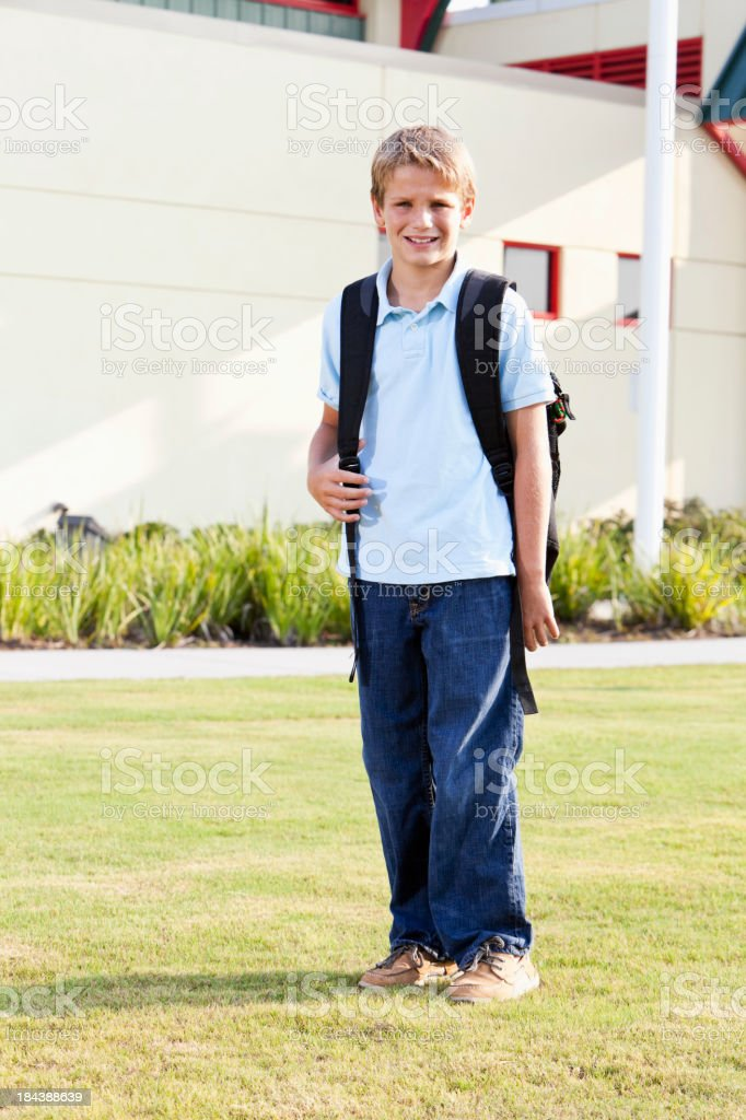 Boy standing outside school with bookbag stock photo