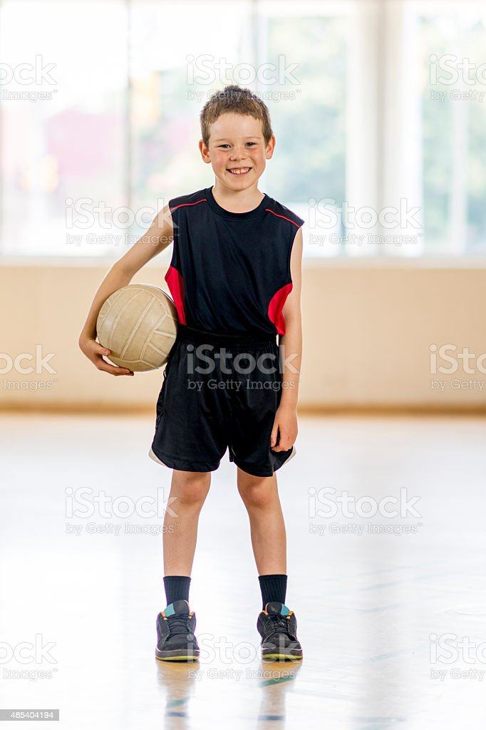 Boy Standing with a Volleyball stock photo