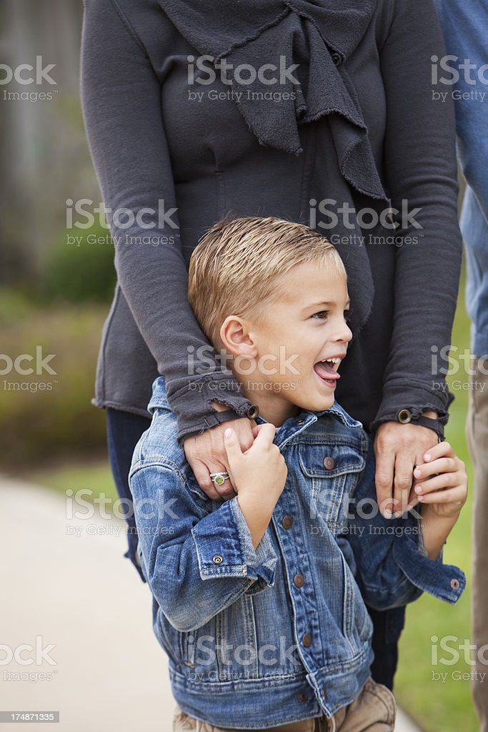 Boy standing with mother outdoors stock photo