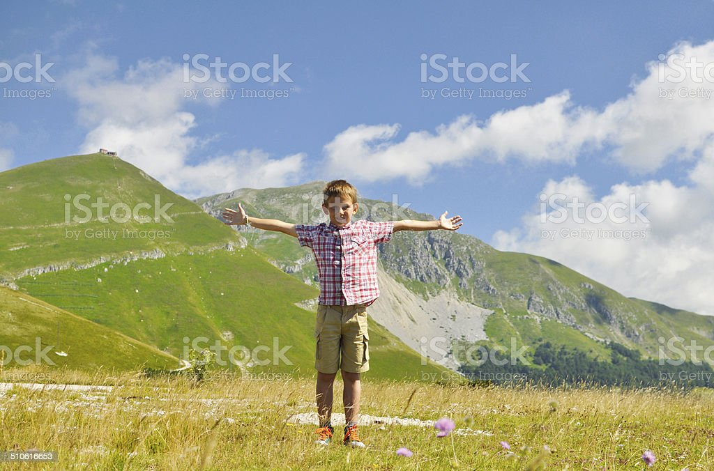 Boy stands in front of the mountains. stock photo