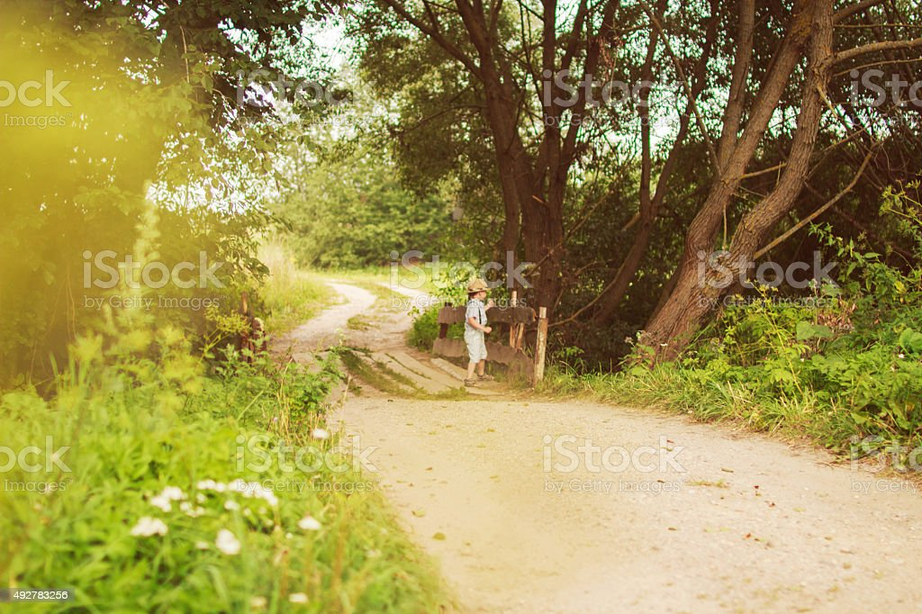 boy stands in the forest on footpath stock photo