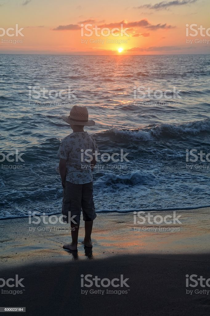 Boy stands on the beach at the sundown stock photo