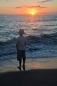 Boy stands on the beach at the sundown