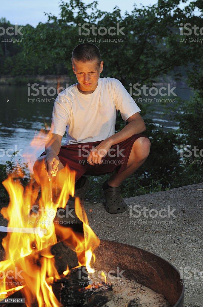 Boy stoking campfire stock photo