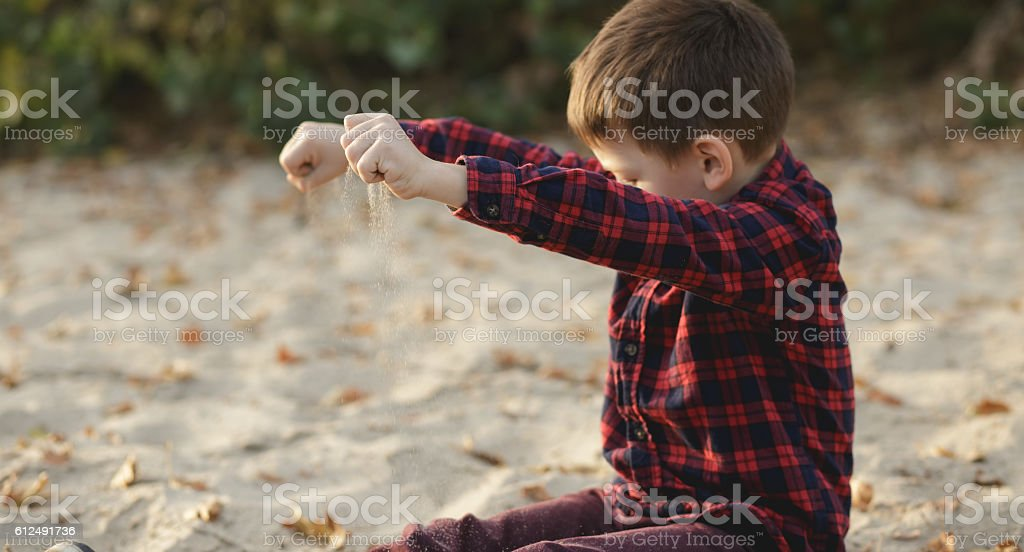 Boy strewing sand outdoor stock photo