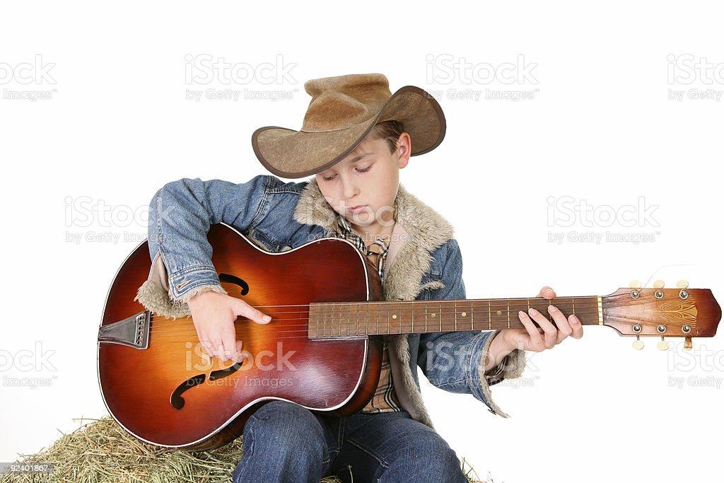 Boy strumming guitar stock photo