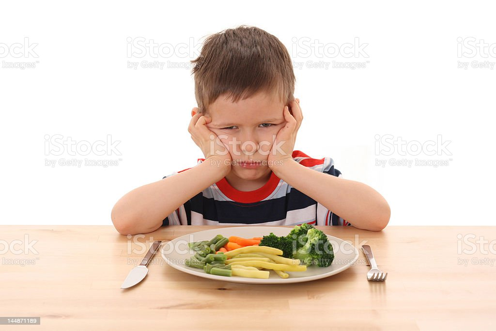 A boy sulking as he doesn't want to eat the vegetables stock photo