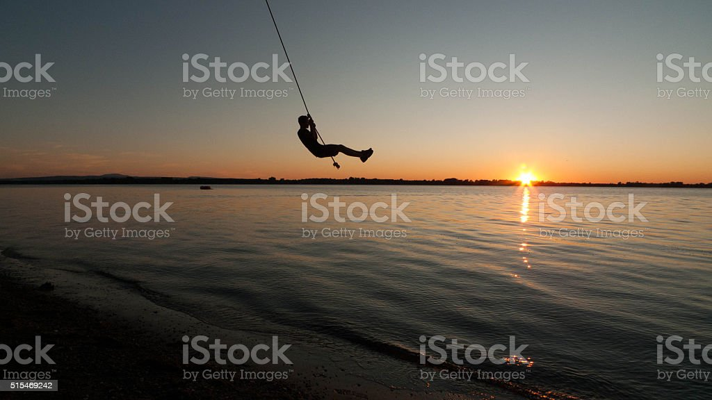 Boy swings from rope stock photo