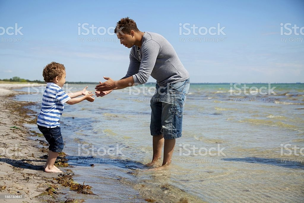 Boy Takes Little Steps Towards His Father stock photo