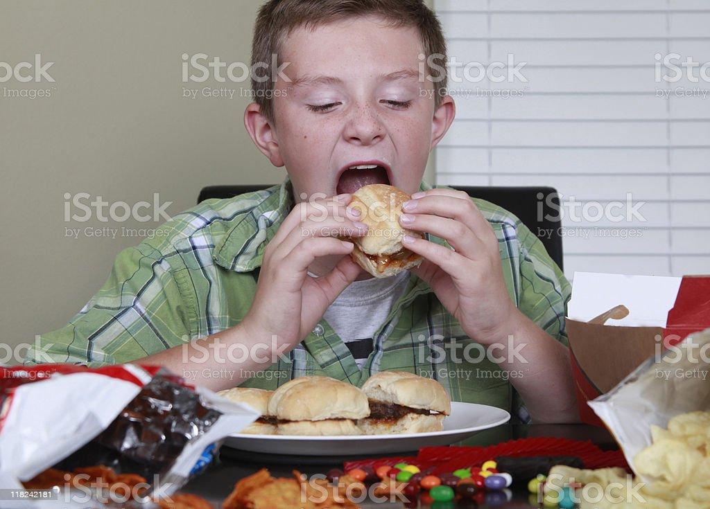Boy Taking a Bit of Burger royalty-free stock photo