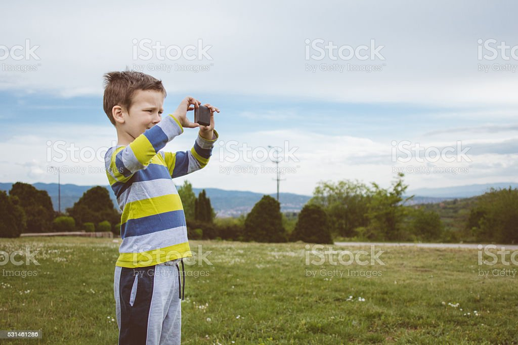 Boy taking phone photo of majestic grassy scenery stock photo