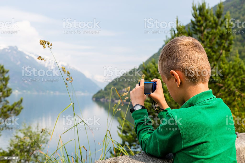 Boy taking picture with digital compact camera stock photo
