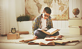 Boy teenager studying, reading books, preparing for exams at hom