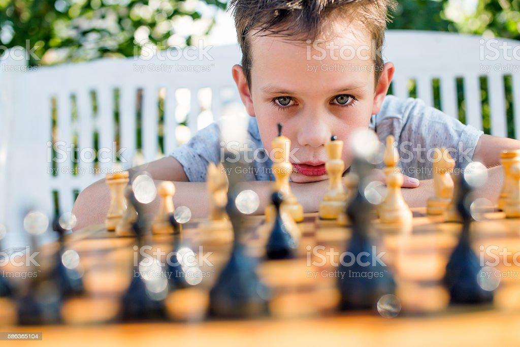 boy thinking hard on chess combinations stock photo
