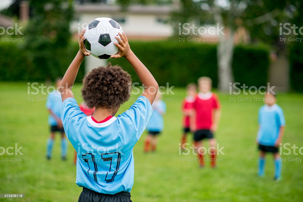 Boy Throwing a Soccer Ball stock photo