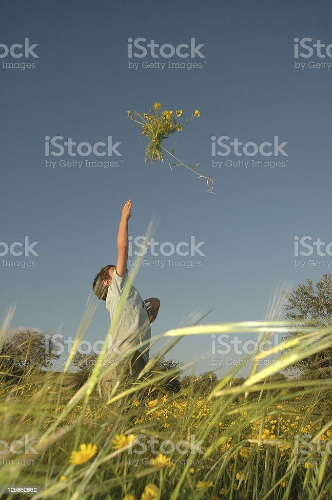 Boy throwing bundle of flowers royalty-free stock photo