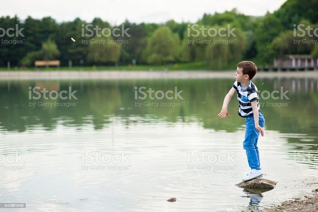 boy throws small stone into the lake stock photo