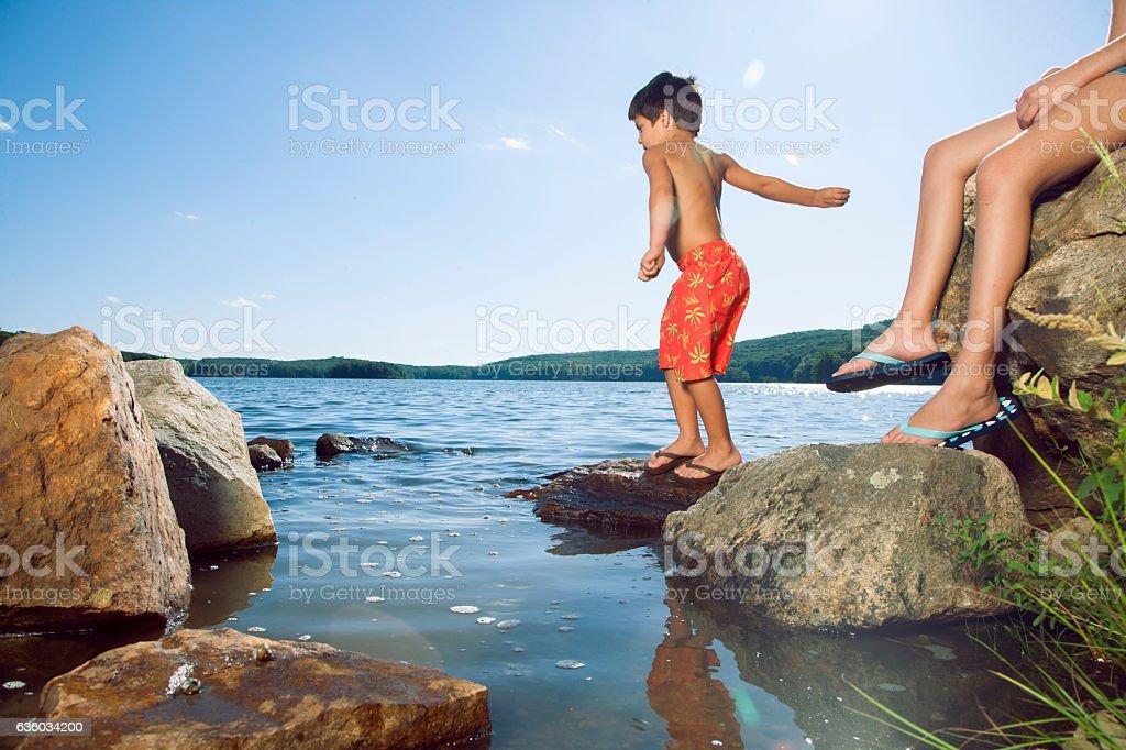 Boy tossing rocks into lake stock photo