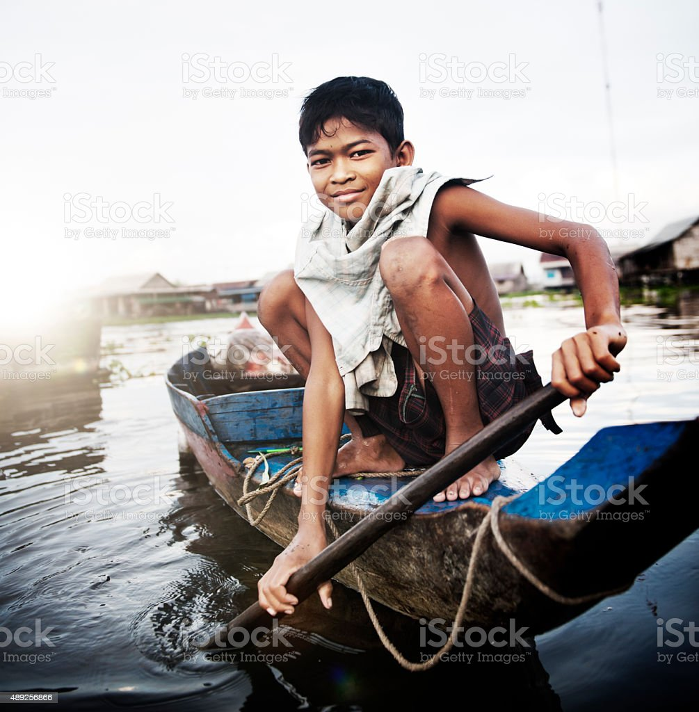 Boy Traveling by Boat in Floating Village Concept stock photo
